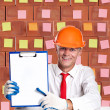 A businessman in working helmet holding sign — Stock Photo