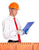The businessman behind a brick wall and read a checklist — Stock Photo