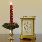 Old bronze clock and red candle — Stock Photo