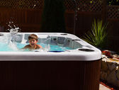 Happy boy playing in jacuzzi on the back yard — Stock Photo