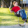 Royalty-Free Stock Photo: Happy young boy playing on swing