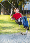 Happy young boy playing on swing — Stock Photo