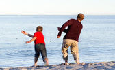 Father and son throwing pebbles into the sea — Stock Photo