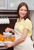 Beautiful woman making orange juice — Stock Photo