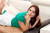 Attactive woman lying on the sofa with laptop — Stock Photo