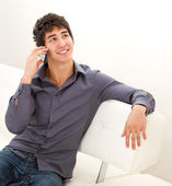 Happy smiling young man sitting on the leather sofa and talking — Stock Photo