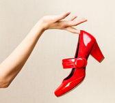Female hand holding red varnish shoes on a high heel. — Stock Photo