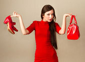Beautiful woman in red dress holding high heel shoes and handbag — Stock Photo
