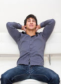 Relaxed man sitting on the leather sofa — Stock Photo