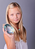 Young girl holding a seashell — Stock Photo