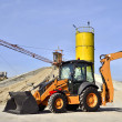 Wheel loader Excavator unloading sand of construction site concrete plant. — Stock Photo