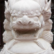 One of stone lions at the base of a pagoda - Stock Photo