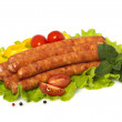 Appetizing grilled sausages on a piece of lettuce with cherry tomatoes, herbs and spices - Stock Photo