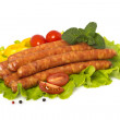 Appetizing grilled sausages on a piece of lettuce with vegetables, herbs and spices — Stok fotoğraf