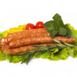 Royalty-Free Stock Photo: Appetizing grilled sausages on a piece of lettuce with vegetables, herbs and spices