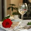 Restaurant table with glasses and rose — Stock Photo