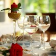 Restaurant table with glasses and rose — Stock Photo #16234069