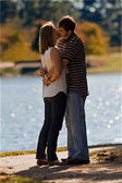 Young Couple In Love Kiss By Glistening Lake — Stock Photo