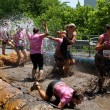 Women Get Hosed Down Running Through Obstacle Course Mud Pit - Stock Photo