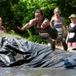 Woman Dives Into Mud Pit On Obstacle Course Run - Stock Photo