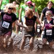Women Splash Around In Mud Pit Of Obstacle Course Run - Stock Photo