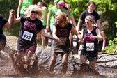 Frauen, plantschen im schlamm grube der hindernis-parcours laufen — Stockfoto