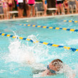 Stock Photo: Child Swimmer Does Freestylel During Swim Meet