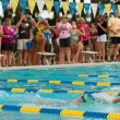 Stock Photo: Youth Swimmer Swims Backstroke As Spectators Look On