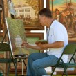 Stock Photo: Artist Works On Painting At Outdoor Festival