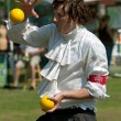Stock Photo: Juggler Balances Ball On Head While Performing At Festival