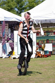 Circus Performer Juggles While Riding Unicycle — Stock Photo
