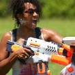 Woman Gets Squirted In Face With Water Gun - Stock Photo