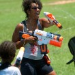 Woman Squirts Other In Water Gun Fight - Stock Photo