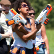 Woman Defiantly Brandishes Weapons Just Before Water Gun Fight - Stock Photo