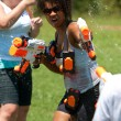 Woman Squirts In Group Water Gun Fight - Stock Photo