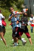 Uomo schizza in lotta di gruppo pistola ad acqua — Foto Stock