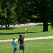 Man And Boy Fly Model Airplane in Park - Stock Photo