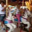 Foto Stock: Motion Blur Of Kids Riding Carousel At Fair