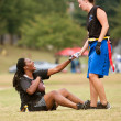 Female Flag Football Player Helps Teammate Get Up - Stock Photo