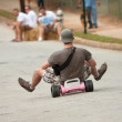 Man Rides Big Wheel Down Hill - Stock Photo