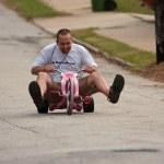 Man Rides Big Wheel Down Steep Hill — Stock Photo