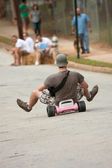 Man Rides Big Wheel Down Hill — Stock Photo