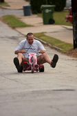 Man Rides Big Wheel Down Steep Hill — Stock Photo
