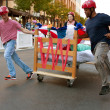 Stock Photo: Team Pushes Bed Through Turn In Odd Mattress Race