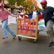 Team Pushes Bed Through Turn In Odd Mattress Race - Stok fotoğraf