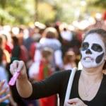 vrouwelijke zombie uitdeelt snoep op halloween parade — Stockfoto