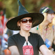 Woman In Witch Hat Walks In Halloween Parade - Stock Photo