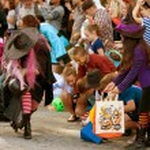 魔女は、ハロウィーン パレードで子供たちにお菓子を手します。 — ストック写真