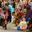 heks snoep uitdeelt aan kinderen op halloween parade — Stockfoto