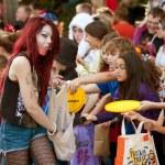 vrouw uitdeelt snoep op halloween parade — Stockfoto